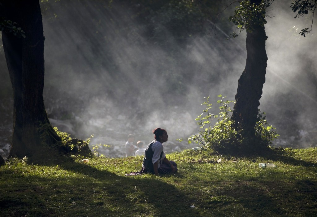 A Romanian gypsy sits on the grass while the Roma community celebrates the Birth of the Virgin Mary in Costesti. AP Photo/Vadim Ghirda