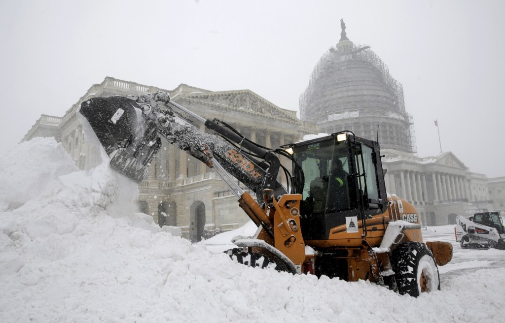 A Capitol Hill employee uses a heavy earth moving machine to clear snow in Washington. REUTERS/Joshua Roberts