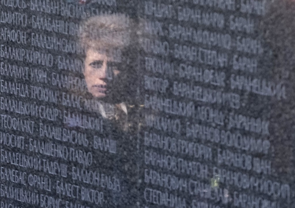 A woman is reflected in a wall with names of victims during a commemoration ceremony at a memorial near Bykovnya, outside Kiev. REUTERS/Gleb Garanich
