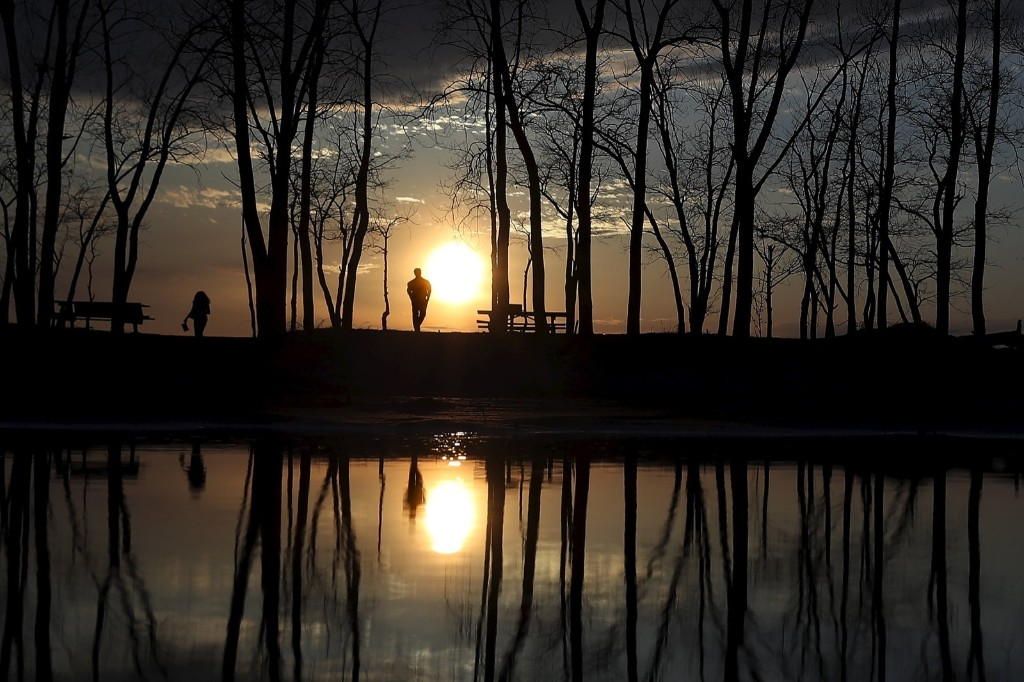 People watch the sun set as they are reflected in a puddle at Presque Isle State Park in Erie, Pa. REUTERS/Carlo Allegri