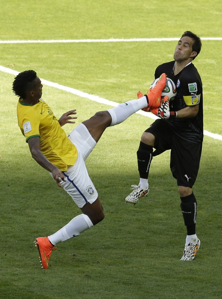 Brazil's Jo kicks the ball in the arms of Chile's goalkeeper Claudio Bravo. AP Photo/Hassan Ammar