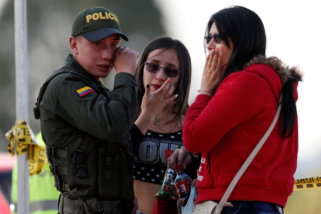 A police officer and two women wipe their tears close to the scene where a car bomb exploded, according to authorities, in Bogota, Colombia January 17, 2019. REUTERS/Luisa Gonzalez