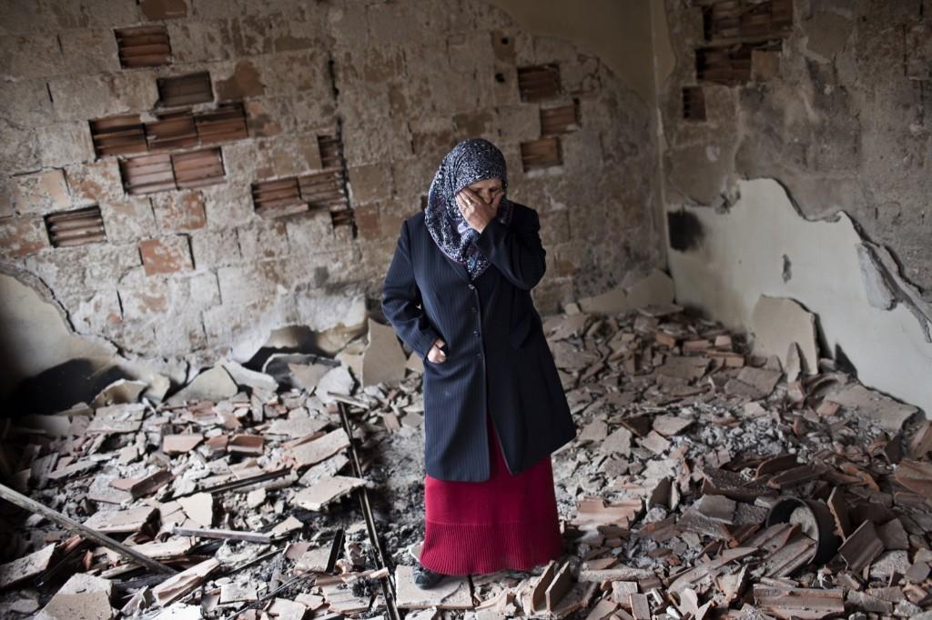 Habibe Biyali stands inside a room in her house heavily damaged by fighting in Kumanovo, Macedonia. AP Photo/Marko Drobnjakovic
