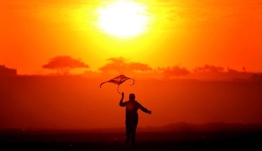 A girl flies a kite as the sun sets in Bnaider, near Kuwait City. YASSER AL-ZAYYAT/AFP/Getty Images