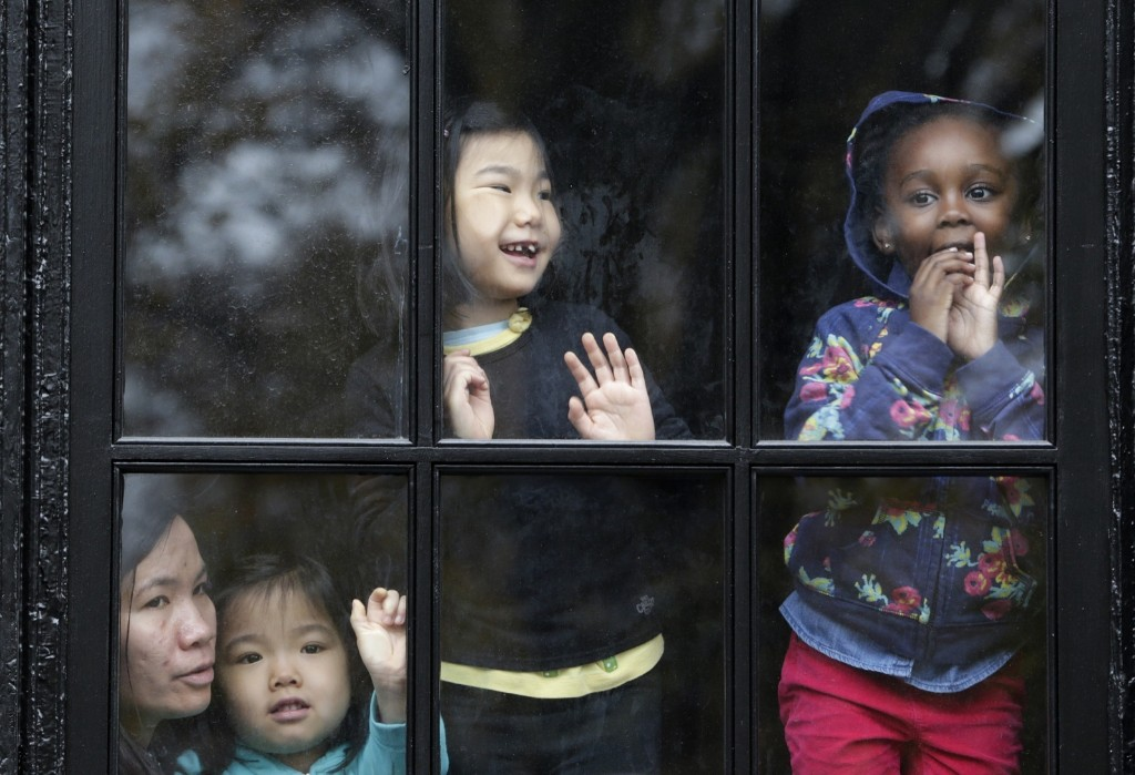 Children watching chilly parade from inside a warm apartment. AP Photo/Julio Cortez