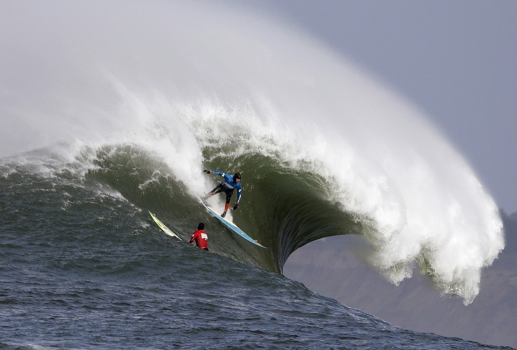 Peter Mel catches a wave as Colin Dwyer, left, watches during the second heat of the first round. Mel is the defending champion. AP Photo/Eric Risberg