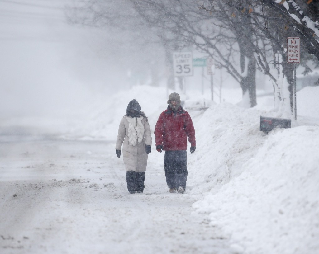 Pedestrians walk along a snow-covered street on Wednesday in Lancaster, New York. AP Photo/Mike Groll