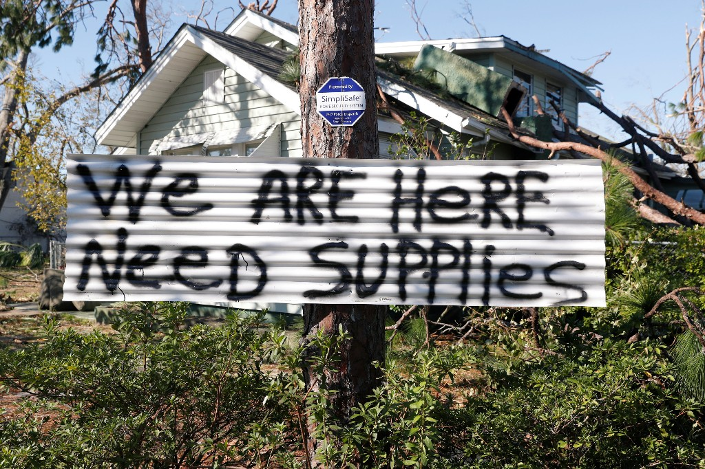 A sign hangs on a tree in front of a house damaged by Hurricane Michael in Panama City, Florida, U.S., October 13, 2018. REUTERS/Terray Sylvester