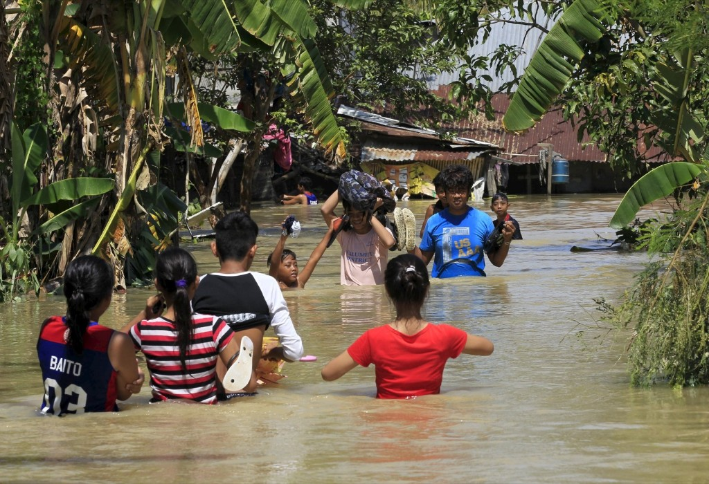 Residents wade across floodwaters after Typhoon Koppu battered Calumpit town, Bulacan province, north of Manila. REUTERS/Romeo Ranoco