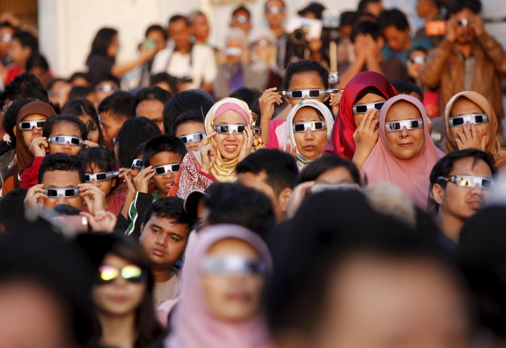 People watch a solar eclipse outside the planetarium in Jakarta, Indonesia. REUTERS/Garry Lotulung