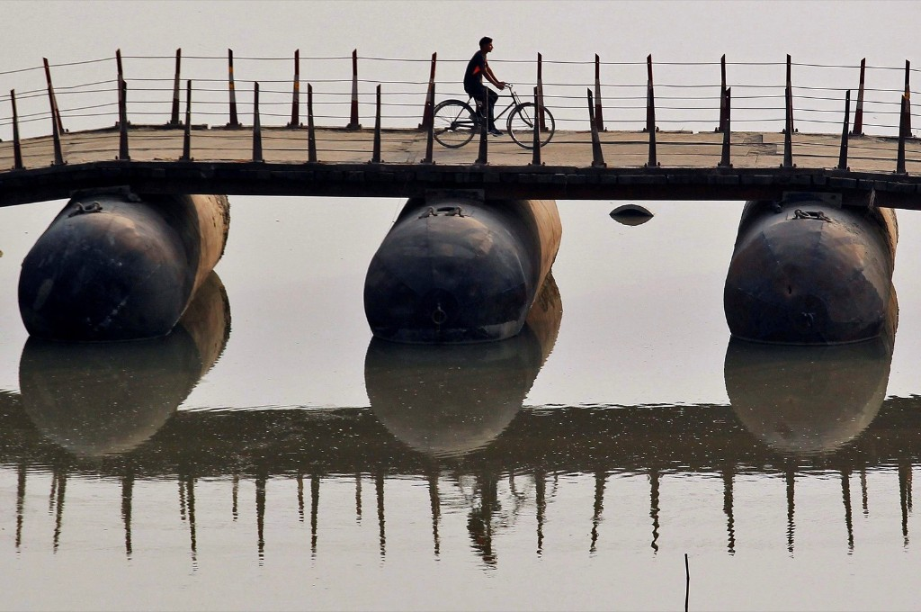 A cyclist crosses a temporary bridge on the banks of the Ganges river in Allahabad, India. REUTERS/Jitendra Prakash