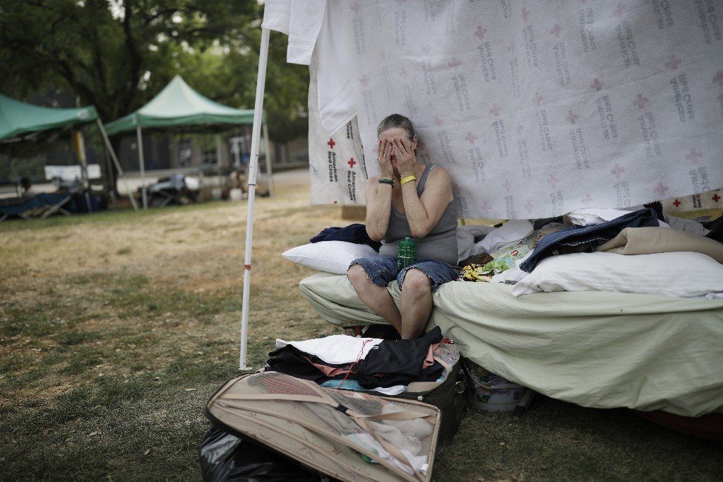 Starla Davis cries as she packs a suitcase in her makeshift tent at an evacuation center Thursday, Aug. 9, 2018, in Redding, Calif. Davis was living with a friend near Whiskytown and had to evacuate because of the Carr Fire. The evacuation center closes on Aug. 10. (AP Photo/John Locher)