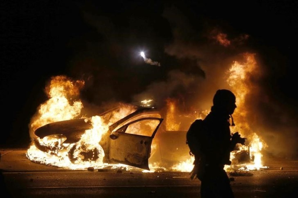 A car burns on the street after a grand jury returned no indictment in the shooting of Michael Brown in Ferguson, Missouri. REUTERS/Jim Young