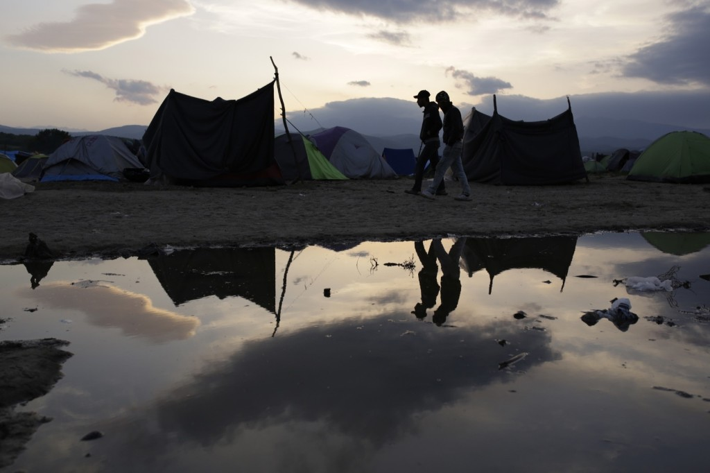 Migrant men are reflected in a pond as they walk among tents at the makeshift camp at the northern Greek border point of Idomeni. AP Photo/Amel Emric