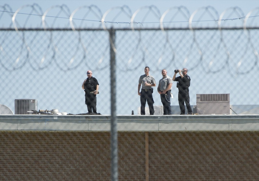 Secret Service and Prison guards stand on the roof as US President Barack Obama tours a cell block at the El Reno Federal Correctional Institution in El Reno, Oklahoma, Thursday. SAUL LOEB/AFP/Getty Images