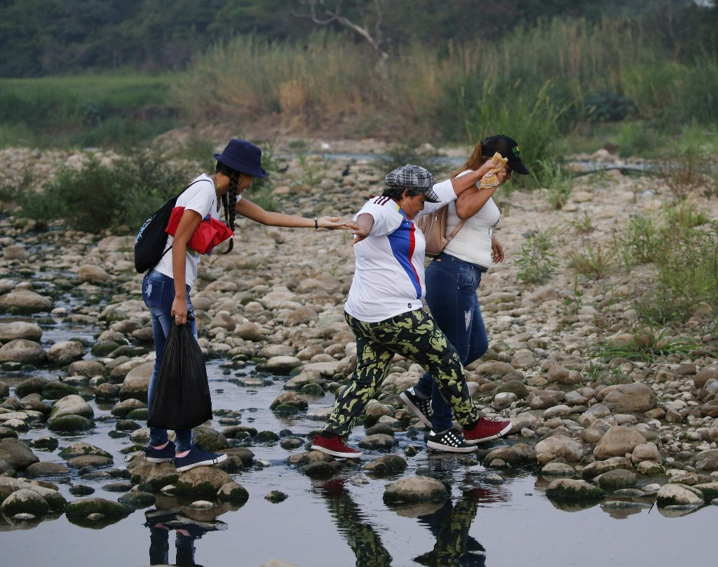 Women cross the Tachira river at the border between Venezuela and Colombia to attend the Venezuela Aid Live concert on the Colombian side of the border, in Palotal, Venezuela, Friday, Feb. 22, 2019. Venezuela's power struggle is set to become a battle of the bands Friday when musicians demanding President Nicolas Maduro allow in humanitarian aid and those supporting his refusal sing in rival concerts being held at both sides of a border bridge where tons of donated food and medicine are stored.(AP Photo/Fernando Llano)