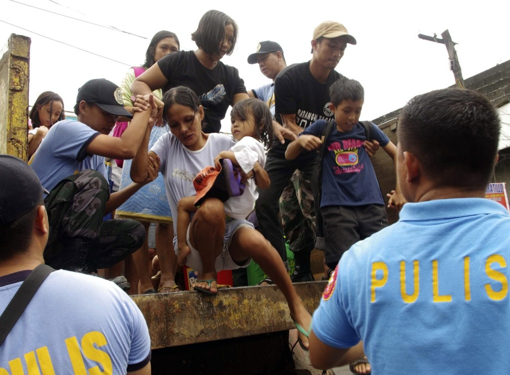 "Residents living near the slopes of Mayon volcano are evacuated to public schools by police. The storm slammed into central Philippine provinces, with one weather expert warning, ""There will be catastrophic damage."" AP Photo/Nelson Salting"