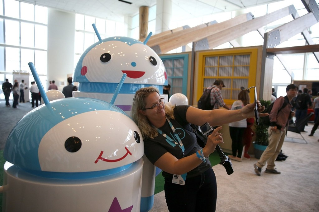 An attendee takes a selfie in front of Android mascots during the 2015 Google I/O conference, Thursday, in San Francisco. Justin Sullivan/Getty Images