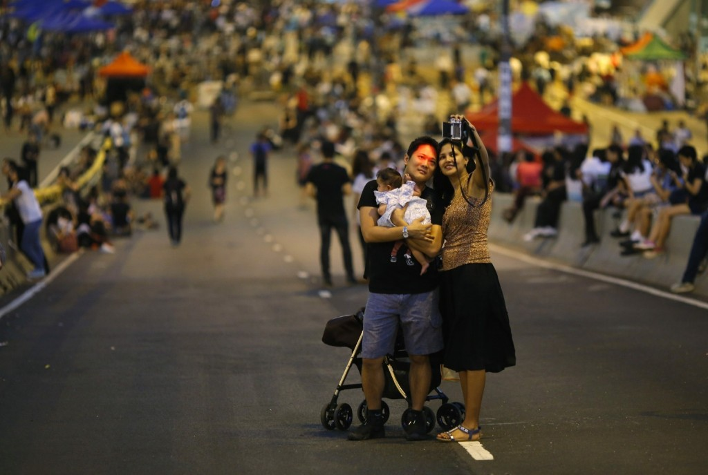 A couple takes a selfie as protesters block an area outside government headquarters in Hong Kong. REUTERS/Carlos Barria