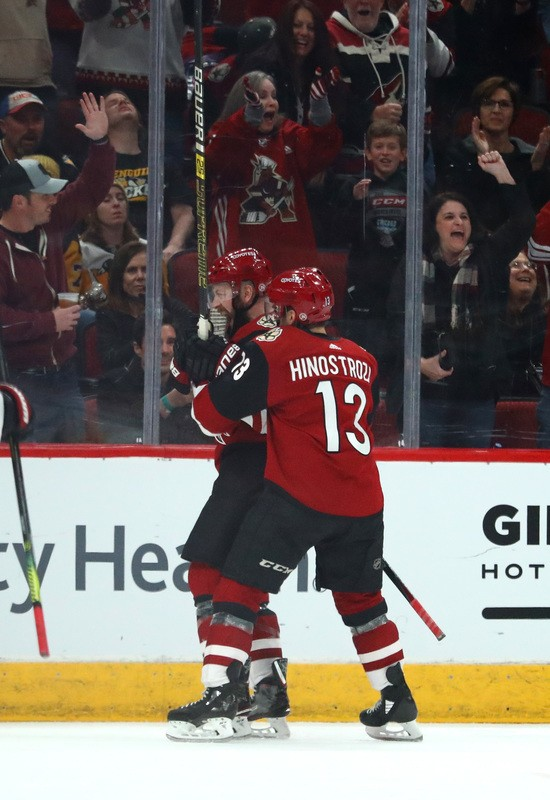 Jan 18, 2019; Glendale, AZ, USA; Arizona Coyotes center Derek Stepan (21) celebrates with center Vinnie Hinostroza (13) after scoring the tying goal against the Pittsburgh Penguins in the third period at Gila River Arena. Mandatory Credit: Mark J. Rebilas-USA TODAY Sports
