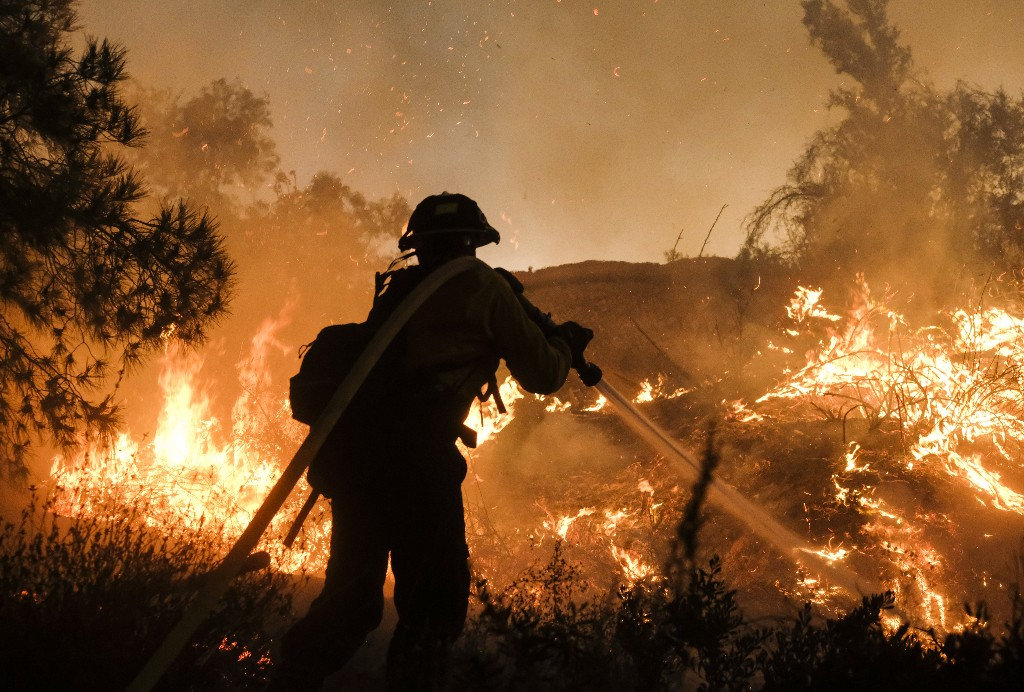 A firefighter battles the Holy Fire burning in the Cleveland National Forest along a hillside at Temescal Valley in Corona, Calif., Thursday, Aug. 9, 2018. Firefighters fought a desperate battle to stop the Holy Fire from reaching homes as the blaze surged through the Cleveland National Forest above the city of Lake Elsinore and its surrounding communities. (AP Photo/Ringo H.W. Chiu)