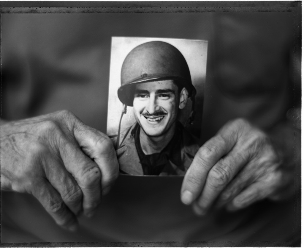 Former 116th Infantry Regiment flame thrower Harry Parley with a vintage photo of himself, 2004. David Burnett/Contact Press Images