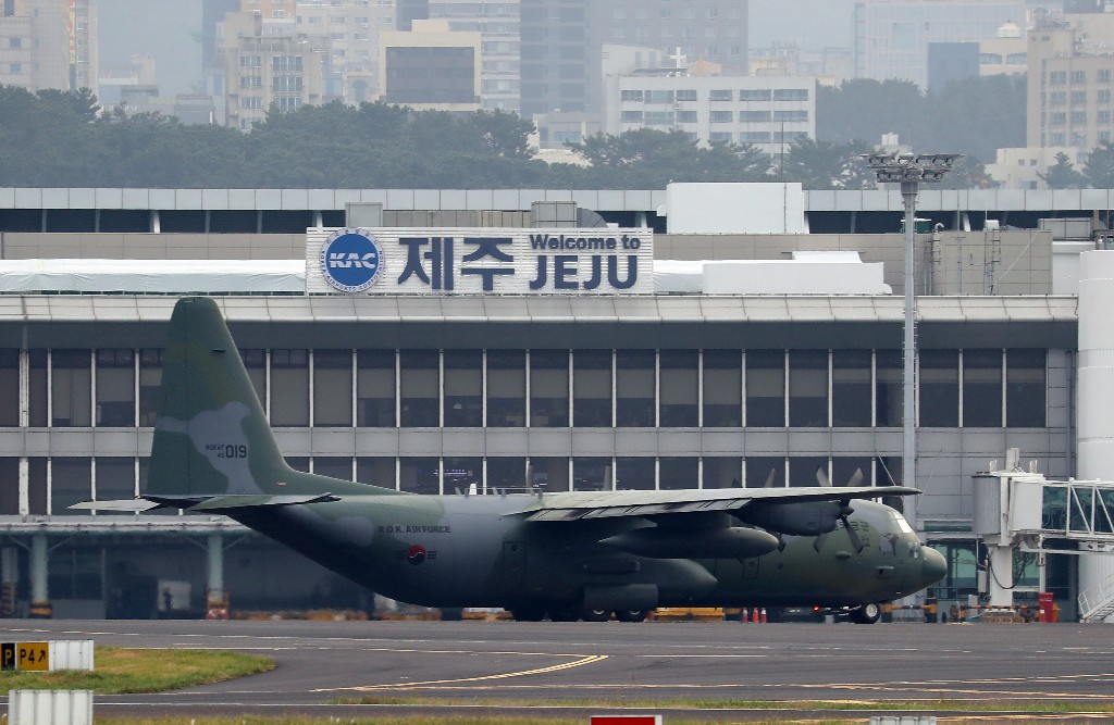 In this Nov. 11, 2018 photo, a South Korea's Air Force cargo plane C-130 carrying boxes of tangerines, is seen before its take off for North Korea at the Jeju International Airport on Jeju Island, South Korea. South Korea has airlifted thousands of boxes of tangerines to North Korea in return for the North's large shipments of pine mushrooms in September.(Park Ji-ho/Yonhap via AP)