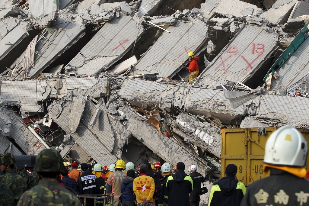 Rescue personnel work at the site where a 17-story apartment building collapsed. REUTERS/Pichi Chuang