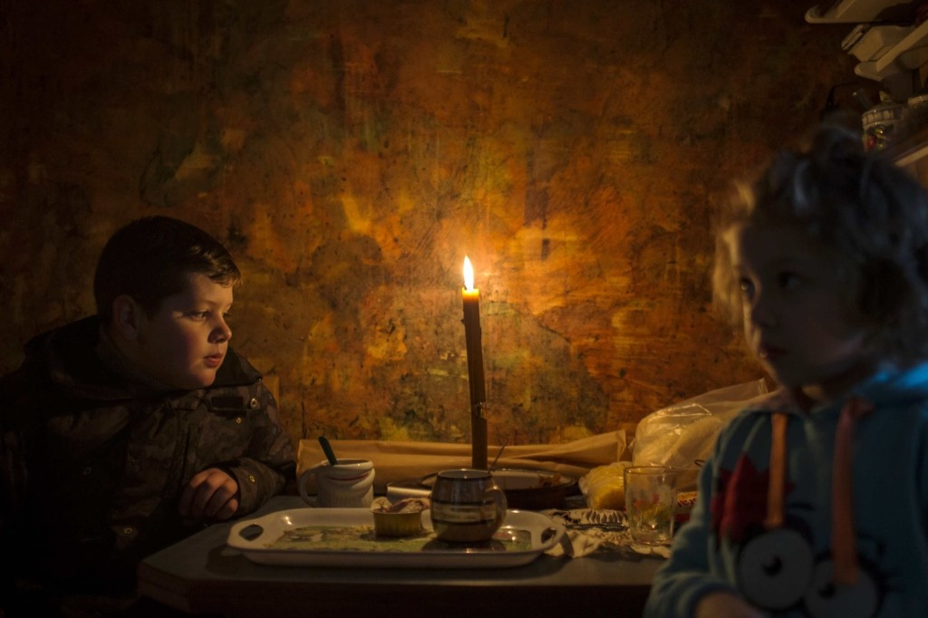 Lazar and his sister Andjelka sit by a candle in their home in the eastern Serbian town of Majdanpek which has been without power, heat or running water for a fourth day. REUTERS/Marko Djurica