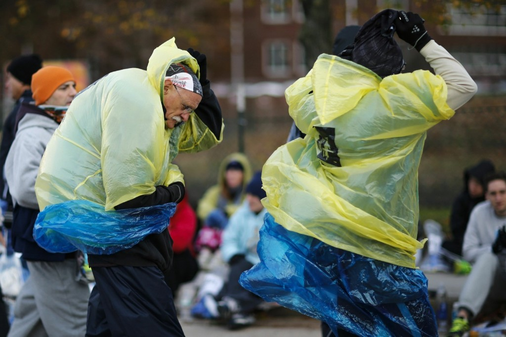 Runners cover themselves from the low temperatures and strong wind before the start. REUTERS/Eduardo Munoz