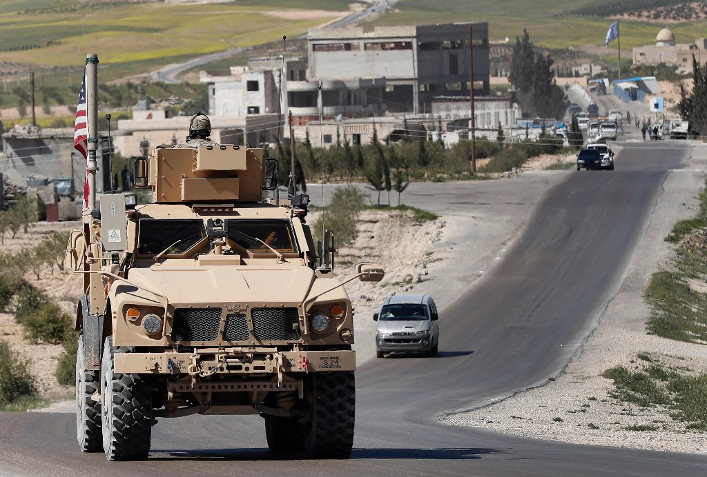 FILE - In this April 4, 2018, file photo, a U.S. soldier sits on an armored vehicle on a road leading to the front line with Turkish-backed fighters, in Manbij, north Syria. The United States' main ally in Syria on Thursday, Dec. 20, 2018, rejected President Donald Trump's claim that Islamic State militants have been defeated and warned that the withdrawal of American troops would lead to a resurgence of the extremist group. (AP Photo/Hussein Malla, File)