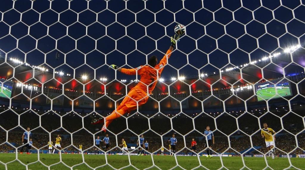 Colombia's James Rodriguez (10) scores a goal against Uruguay's goalkeeper Fernando Muslera. REUTERS/Kai Pfaffenbach