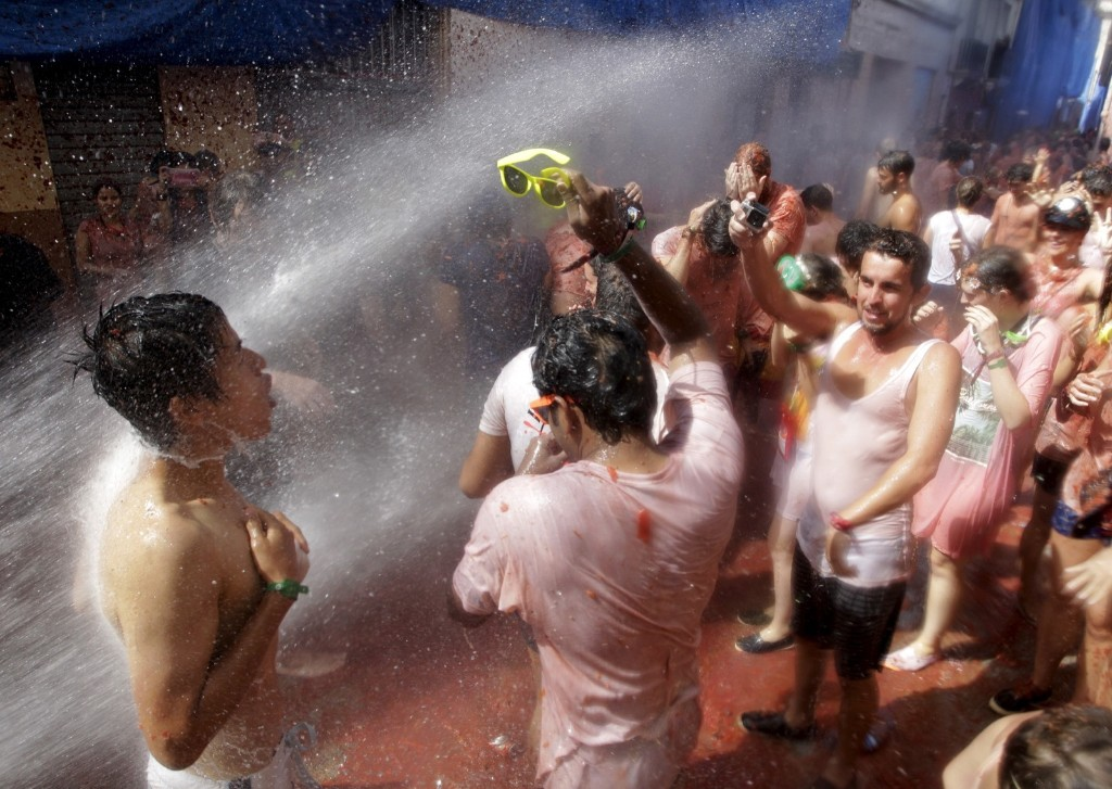"Revelers are sprayed with water after the annual ""Tomatina"" (tomato fight) in Bunol, near Valencia, Spain, Wednesday. REUTERS/Heino Kalis"