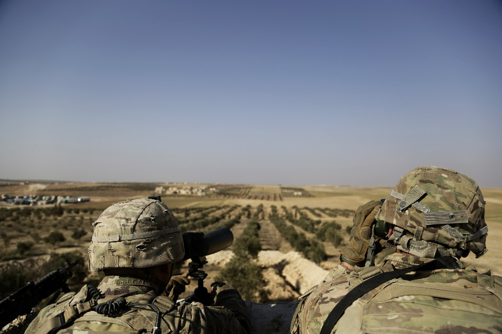 FILE - In this February 7, 2018 file photo, American troops look out toward the border with Turkey from a small outpost near the town of Manbij, northern Syria. The United States' main ally in Syria on Thursday, Dec. 20, 2018, rejected President Donald Trump's claim that Islamic State militants have been defeated and warned that the withdrawal of American troops would lead to a resurgence of the extremist group.(AP Photo/Susannah George, File)