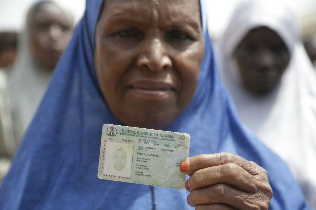 A woman displays her voters card before casting her votes during the Presidential and National Assembly election in Damilu Yola, Nigeria, Saturday, Feb. 23, 2019. Africa's most populous country goes to the polls on Saturday to decide whether President Muhammadu Buhari deserves a second term. While more than 70 people are running to lead Nigeria, the close race comes down to Buhari and a billionaire former vice president, Atiku Abubakar. (AP Photo/Sunday Alamba)