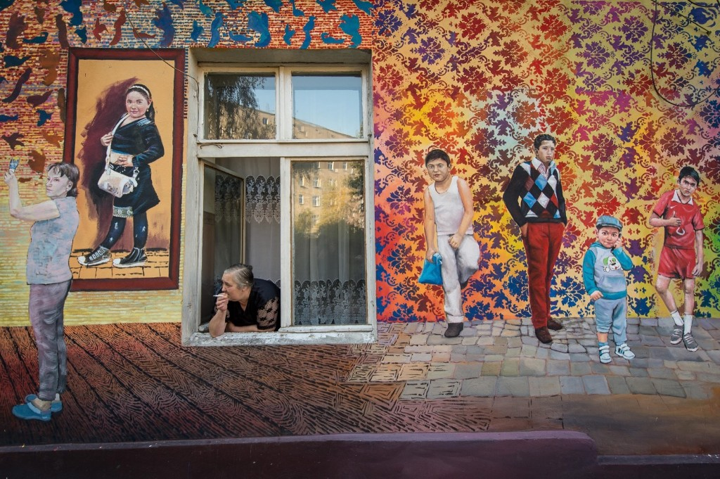 A resident looks out from a window of a building with a mural in one of the courtyards in Wroclaw, Poland. EPA/MACIEJ KULCZYNSKI