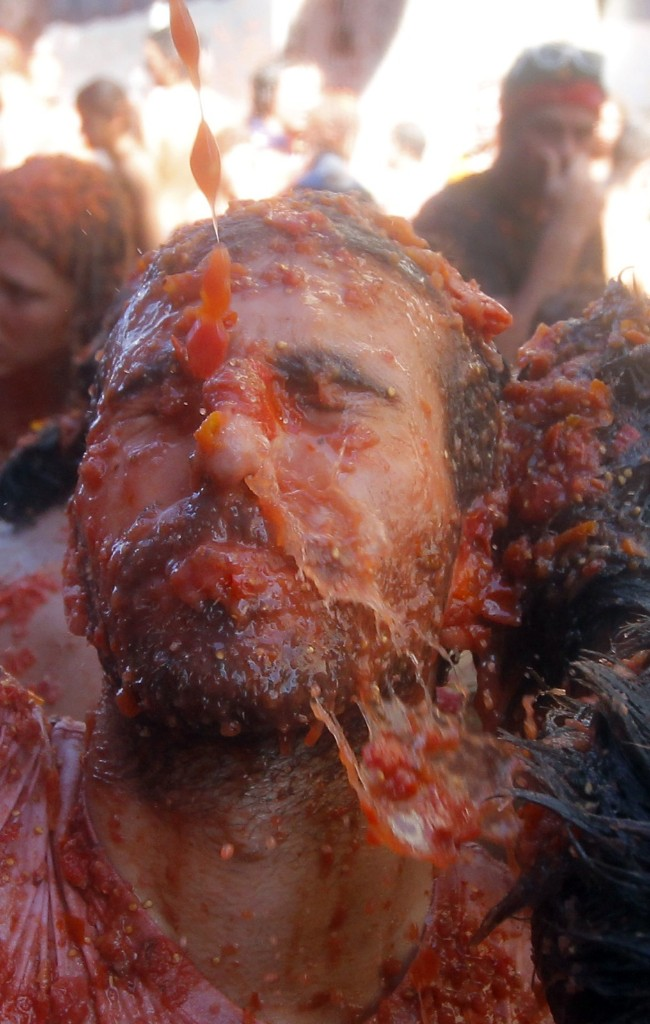 A man is hit with tomatoes during the morning festivities. AP Photo/Alberto Saiz