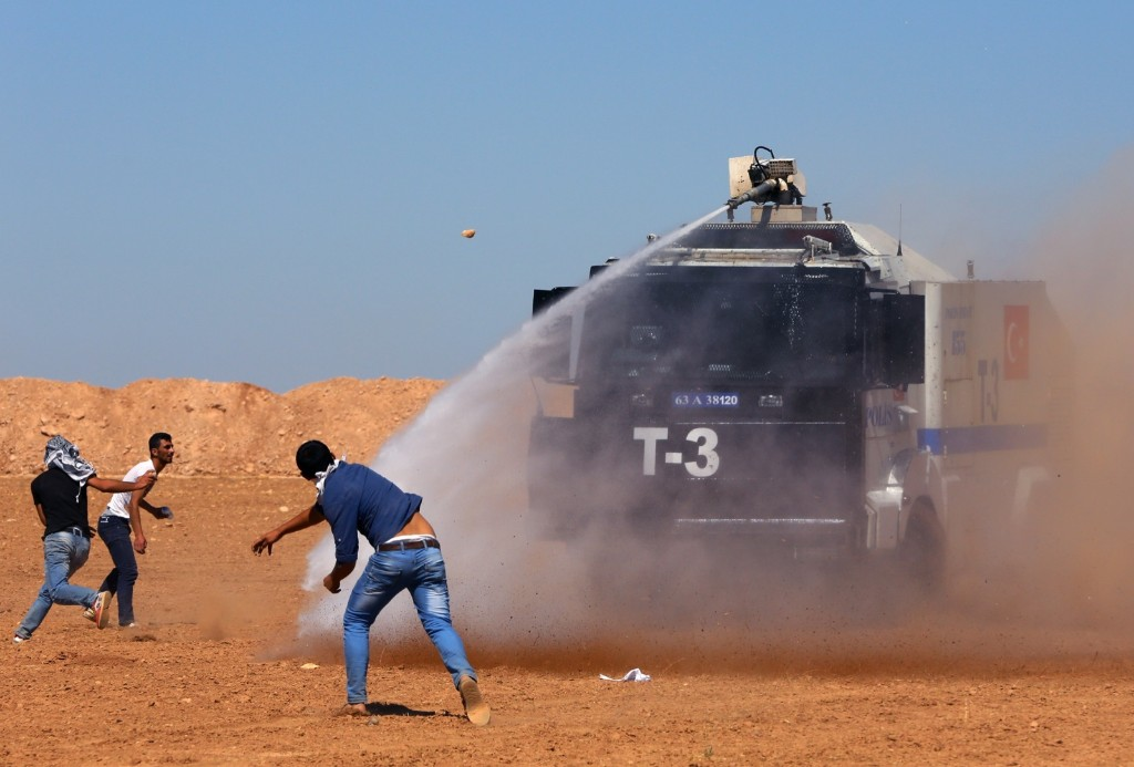 Turkish security forces use teargas and water cannons to disperse Kurdish demonstrators as several hundred Syrian refugees wait at the border in Suruc. AP Photo/Burhan Ozbilici