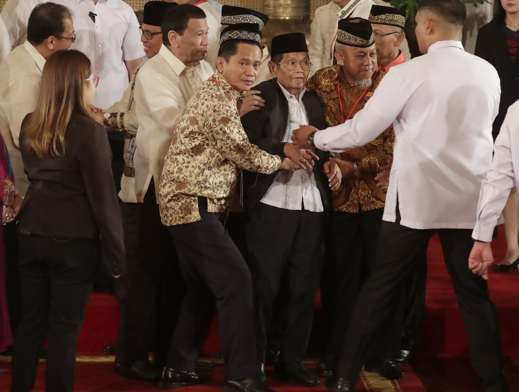President Rodrigo Duterte, third from left, helps in assisting Ghazali Jaafar, Vice-chair for Political Affairs and Chair of the Bangsamoro Transition Commission, after briefly falling following oath-taking ceremony for the creation of the Bangsamoro Transition Authority or BTA at the Presidential Palace in Manila, Philippines Friday, Feb. 22, 2019. Some of the fiercest Muslim rebel commanders in the southern Philippines are in Manila to be sworn in as administrators of a new Muslim autonomy region in a delicate milestone to settle one of Asia's longest-raging rebellions. Several commanders, including Commander Bravo, long wanted for deadly attacks were given safety passes to be able to travel to Manila and join the ceremony.(AP Photo/Bullit Marquez)