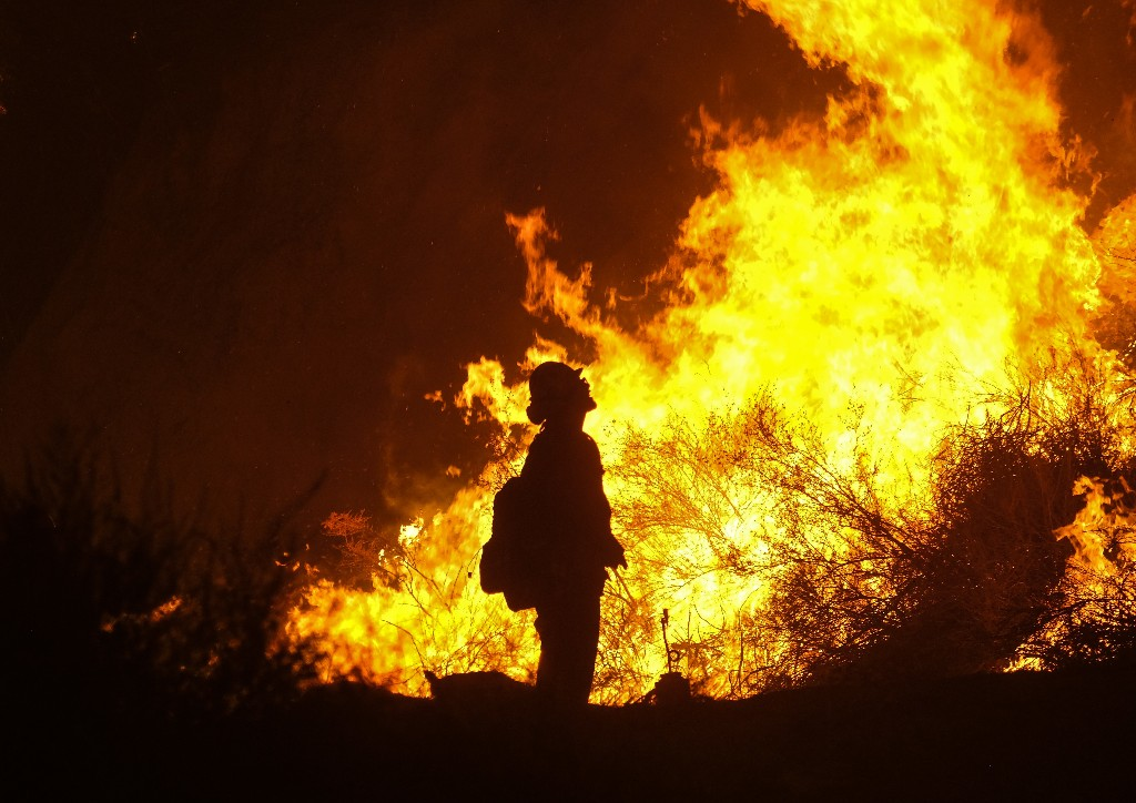 A firefighter keeps watch as the Holy Fire burns in the Cleveland National Forest along a hillside at Temescal Valley in Corona, Calif., Thursday, Aug. 9, 2018. Firefighters fought a desperate battle to stop the Holy Fire from reaching homes as the blaze surged through the Cleveland National Forest above the city of Lake Elsinore and its surrounding communities. (AP Photo/Ringo H.W. Chiu)