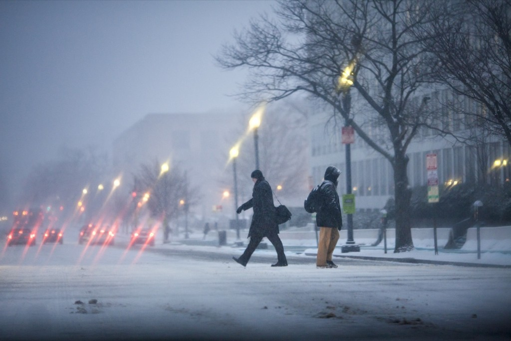 People make their way to work in Washington during the first snowfall of the year and the opening day for the 114th Congress. AP Photo/J. Scott Applewhite