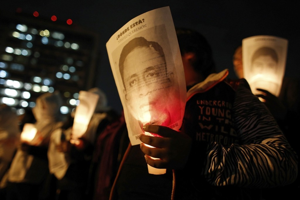 A woman holds a candle and a picture of one of the 43 slain trainee teachers during a march in Mexico City. REUTERS/Tomas Bravo