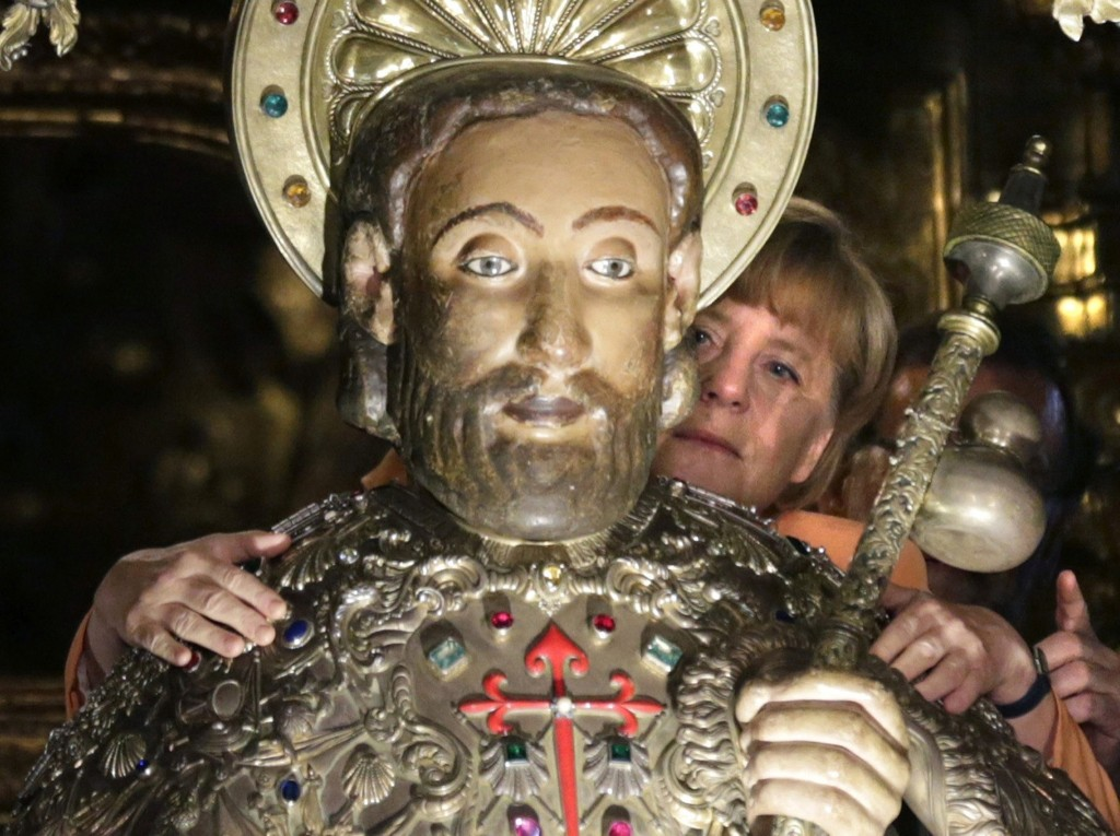 German Chancellor Angela Merkel embraces the statue of Saint James in the cathedral at Santaigo de Compostela. EFE/Pool/Getty Images