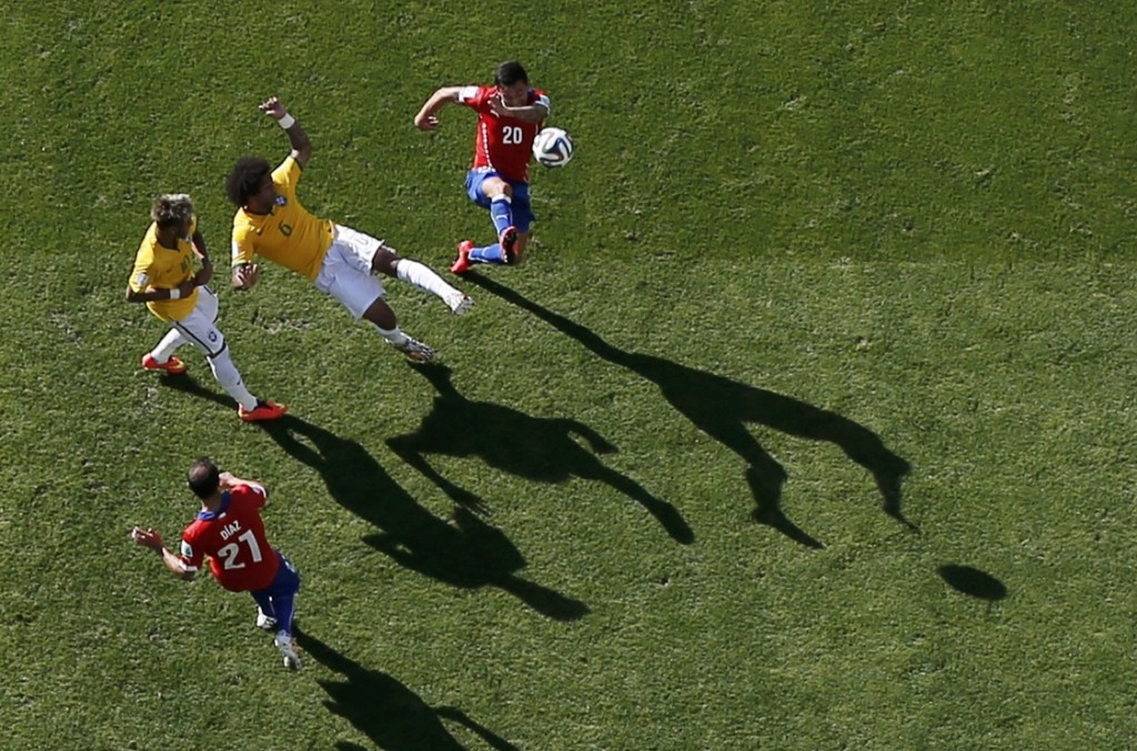 Chile's Charles Aranguiz (20) fights for the ball with Brazil's Marcelo (6). REUTERS/Peter Jebautzke