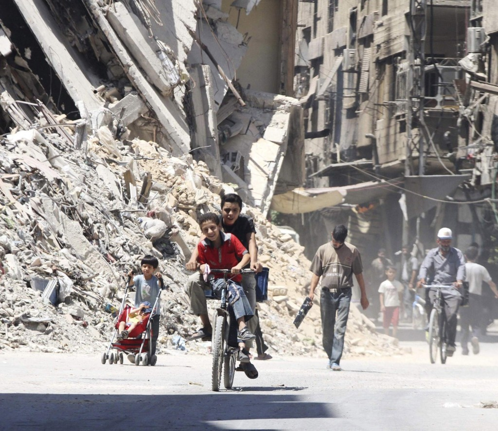 Boys ride a bicycle near damaged buildings in the Damascus suburb of Harasta. REUTERS/Badra Mamet