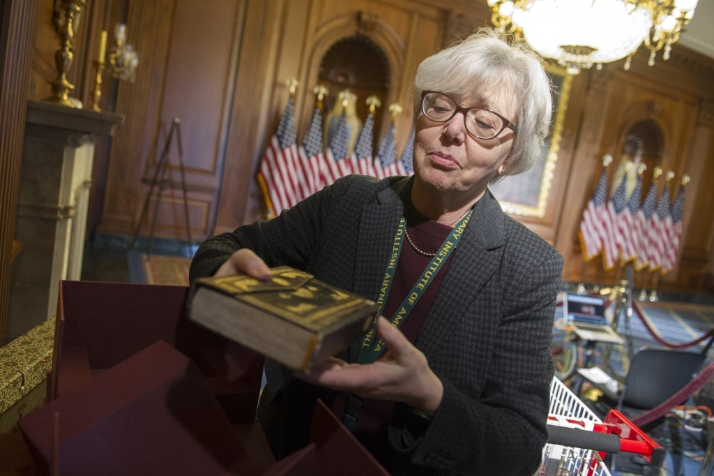 Pam Russell, legislative attorney, Library of Congress, with a Koran as she lays out sacred text for use during ceremonial swearing-in. AP Photo/Cliff Owen
