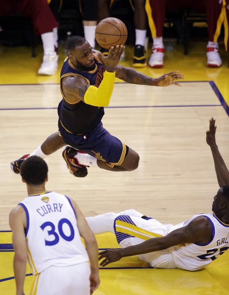 LeBron James shoots over Warriors forward Draymond Green. AP Photo/Eric Risberg