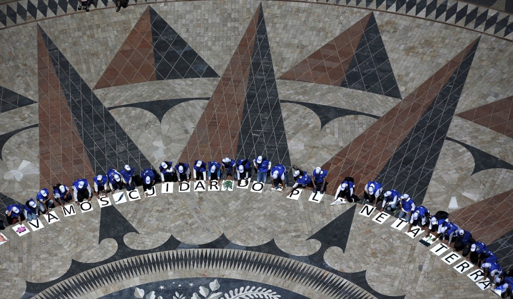 A group of volunteers gather on a square decorated with a giant world map during Earth Day celebrations in Lisbon. REUTERS/Rafael Marchante