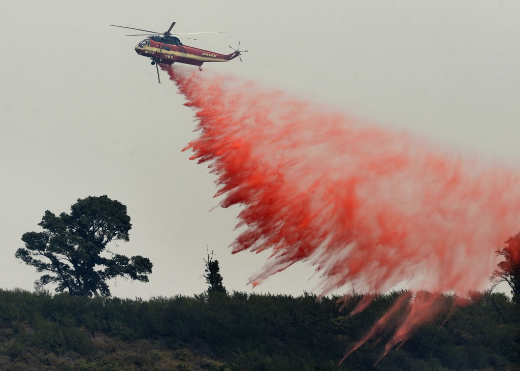 """FILE - In this Aug. 13, 2016 file photo, a fire attack helicopter makes a retardant drop during a firing operation on the ridge between Mount Manuel and the Coast Ridge Road while fighting the Soberanes Fire near the village of Big Sur, Calif. The so-called Soberanes Fire burned its way into the record books as the most expensive wildland firefight in U.S. history in what a new report calls """"an extreme example of excessive, unaccountable, budget-busting suppression spending that is causing a fiscal crisis in the U.S. Forest Service."""" (David Royal/The Monterey County Herald via AP, File)"""