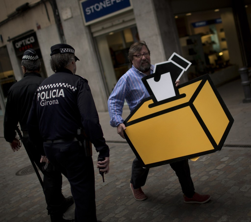 Businessman Emilio Busquets holds a drawing of a ballot box to decorate his shop ahead of voting scheduled for next Sunday in Girona, Spain. AP Photo/Emilio Morenatti